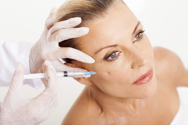 doctor giving mid age woman face lifting injection